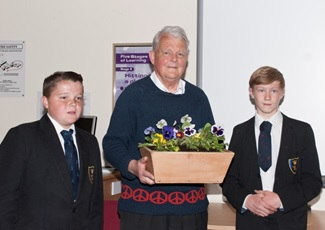 Bruce being presented with a window box made by two younger students